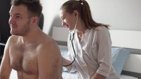 Härlig doktor i ett vitt lag som lyssnar till en stetoskop av en sjuk man arkivfilmer
