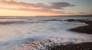 Härlig dramatisk solnedgång över en stenig kust Fotografering för Bildbyråer