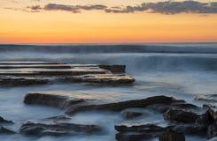 Härlig dramatisk solnedgång över en stenig kust arkivbilder