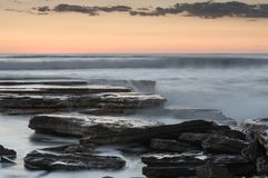 Härlig dramatisk solnedgång över en stenig kust Royaltyfri Fotografi