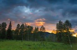 Härlig dramatisk solnedgång i bergen Landskap med solljus som skiner till och med orange moln Royaltyfria Bilder