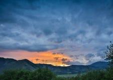 Härlig dramatisk solnedgång i bergen Landskap med solljus som skiner till och med orange moln Royaltyfria Foton