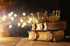 härlig drottning-/konungkrona på den gamla boken Filtrerad tappning medeltida period för fantasi Royaltyfri Bild