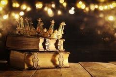 härlig drottning-/konungkrona på den gamla boken Filtrerad tappning medeltida period för fantasi fotografering för bildbyråer