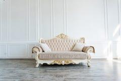Härlig dyr beige soffa mot en vit vägg i ett tomt rum arkivbilder