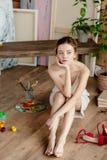härlig eftertänksam ung konstnär som sitter på golv och bort ser fotografering för bildbyråer