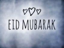 Härlig eid mubarak önskar på isen som ser bakgrund med tre hjärtor arkivfoto