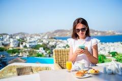 Härlig elegant dam på frukosten med telefonen på det utomhus- kafét med fantastisk sikt på den Mykonos staden fotografering för bildbyråer