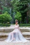 Härlig elegant flicka i aftonklänning med den festliga frisyren för härlig afton nära springbrunnen Royaltyfria Foton