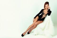 Härlig elegant flicka med den stora bröstsvartbodysuiten i studion på en vit bakgrund med en härlig makeup med långa ben Royaltyfri Bild