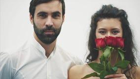 Härlig elegant grabb i en klassisk skjorta med röda rosor i hans händer Syns på en vit bakgrund Ger rosorna till stock video