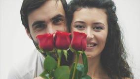 Härlig elegant grabb i en klassisk skjorta med röda rosor i hans händer Syns på en vit bakgrund Ger rosorna till lager videofilmer