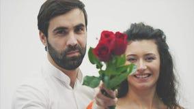 Härlig elegant grabb i en klassisk skjorta med röda rosor i hans händer Syns på en vit bakgrund Ger rosorna till arkivfilmer