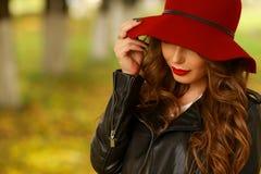 Härlig elegant kvinna i trendig röd hatt i en parkera i höst Arkivfoto