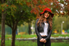 Härlig elegant kvinna i trendig röd hatt i en parkera i höst, Arkivbild