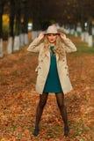 Härlig elegant kvinna som står full längd i trendig beige hatt i en parkera i höst Arkivbild