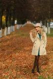 Härlig elegant kvinna som står full längd i trendig beige hatt i en parkera i höst fritt avstånd Begreppshöst Rova och en fallen  Royaltyfri Fotografi