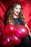 Härlig elegant lycklig ung kvinna med röda bollar i händer med röd läppstift fotografering för bildbyråer