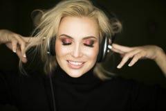 Härlig emotionell högt sjungande kvinna som lyssnar musiken i trådlöst tecken för headphone- och handvisning V på mörker royaltyfri fotografi