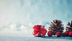 Härlig enkel julbakgrund med kopieringsutrymme Gullig julklapp röda prydnader och att sörja kottar på blå bakgrund royaltyfria bilder