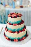 Härlig enorm bröllopstårta med blommor och frukter royaltyfri fotografi