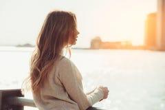 Härlig ensam flicka som drömmer och tänker, medan vänta på datumet i stadshavpir på solnedgångtid Arkivbild
