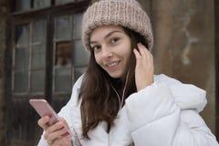Härlig europeisk flicka i ett vitt omslag och en stucken hatt som lyssnar till musik med hörlurar som går runt om staden på arkivbilder