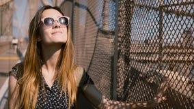 Härlig europeisk kvinna i stilfull solglasögon som går till kameran, rörande hår på staketet 4K för skugga för Brooklyn bro stock video