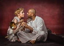 Härlig europeisk kvinna och attraktiv kubansk trombonspelare Royaltyfri Bild