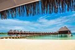 Härlig exotisk strand och träbro till att förbluffa exotiska bungalower på turkosvatten arkivfoto