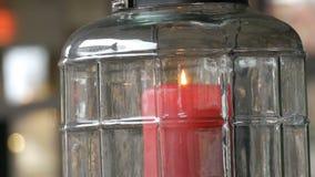 Härlig exponeringsglasljusstake med en stor röd brinnande vaxstearinljus av röd färg som är inom ljusstaken och står på arkivfilmer