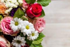 Härlig färgrik bukett av blommor från rosor, kamomillar och grönska på tabellen Arkivfoto