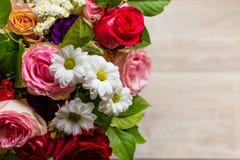 Härlig färgrik bukett av blommor från rosor, kamomillar och grönska på tabellen Arkivbilder