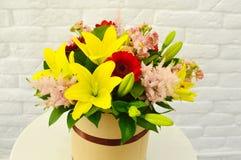 Härlig färgrik bukett av blommor i en hattask arkivbilder