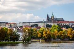 Härlig färgrik höstcityscapesikt av den Prague slotten som ses från floden arkivbilder