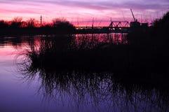 Härlig färgrik skymning på en flod Arkivbild