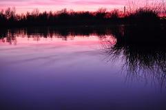 Härlig färgrik skymning på en flod Arkivbilder