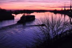 Härlig färgrik skymning på en flod med konturer av fartyget och pråm Royaltyfri Foto
