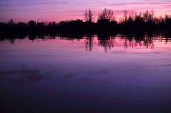 Härlig färgrik skymning på en flod med konturer av hus och träd Arkivbilder