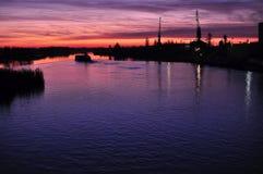 Härlig färgrik skymning på en flod med konturer av pråm och kranar Arkivbilder