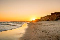 Härlig färgrik solnedgång i Algarve Portugal Fridsamt strandvatten och klippor arkivfoto