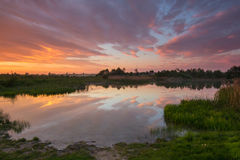 Härlig färgrik solnedgång på countrisidesjön Arkivfoto