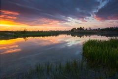 Härlig färgrik solnedgång på countrisidesjön Arkivfoton