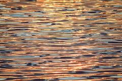 Härlig färgrik vattenyttersida med vågor på solnedgången Royaltyfri Foto