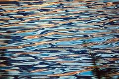 Härlig färgrik vattenyttersida med vågor på solnedgången Arkivfoto