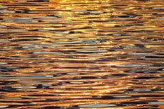 Härlig färgrik vattenyttersida med vågor på solnedgången Fotografering för Bildbyråer