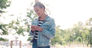 Härlig för grov bomullstvillomslaget för den unga kvinnan bärande maskinskrivning på telefonen i en stad parkerar Royaltyfri Bild