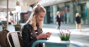 Härlig för läderomslag för ung kvinna bärande maskinskrivning på telefonen under solig dag Royaltyfria Foton
