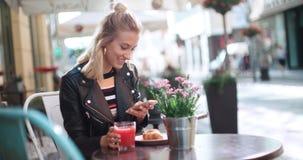 Härlig för läderomslag för ung kvinna bärande maskinskrivning på telefonen under solig dag Arkivbild