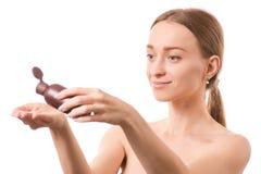 Härlig för skönhetflaska för ung kvinna framsida med skönhetsmedel för olje- lotion för kropp och för framsida arkivfoto